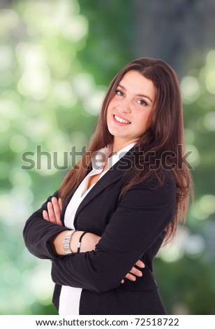 Portrait of a smiling businesswoman. Green out of focus background. - stock photo