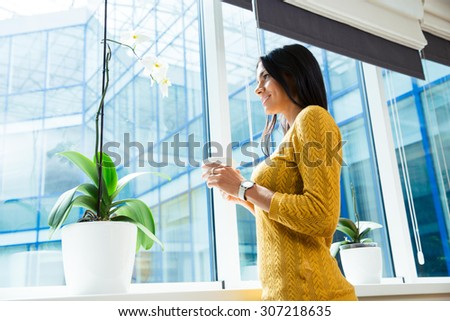 Portrait of a smiling businesswoman holding cup with coffee and looking at window in office - stock photo