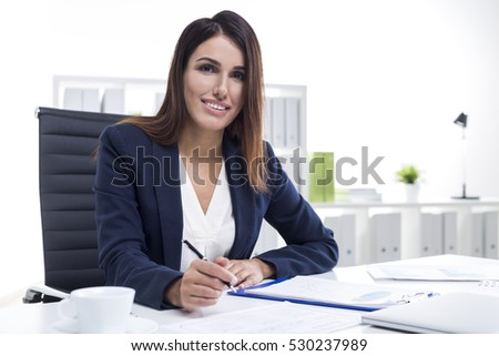 Portrait of a smiling businesswoman in a suit working at her white table in office. She is reading documents and taking notes.