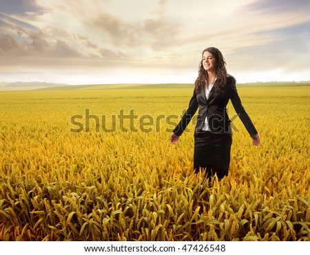 Portrait of a smiling businesswoman standing on a cornfield - stock photo