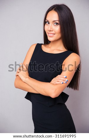 Portrait of a smiling businesswoman standing with arms folded over gray background and looking at camera - stock photo