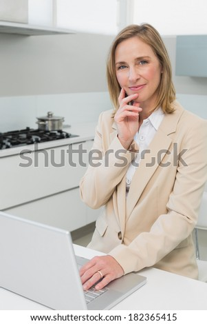 Portrait of a smiling businesswoman using laptop in the kitchen at home