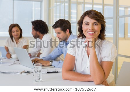 Portrait of a smiling businesswoman with colleagues in meeting at the office