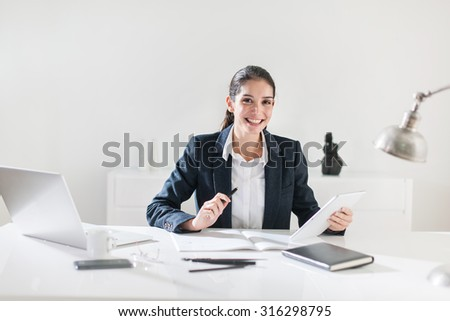 Portrait of a smiling businesswoman with dark hair sitting at her white desk in her office. She is wearing a black suit jacket, designing on her tablet, her laptop, coffe and glasses next to her