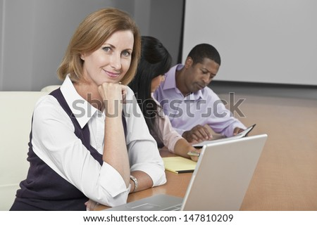 Portrait of a smiling businesswoman with laptop and multiethnic colleagues in conference room - stock photo