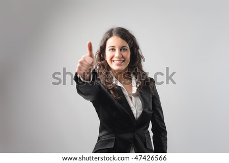 Portrait of a smiling businesswoman with thumbs up - stock photo