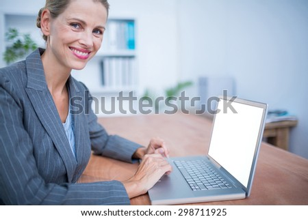 Portrait of a smiling businesswoman working on laptop - stock photo