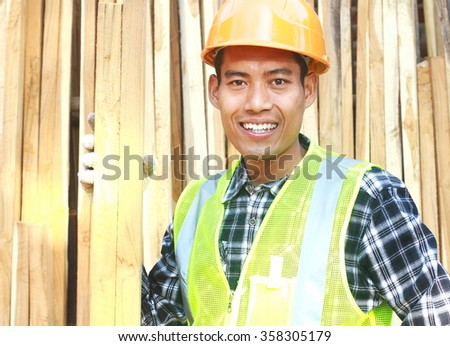 Portrait of a smiling carpenter holding wood look on your camera