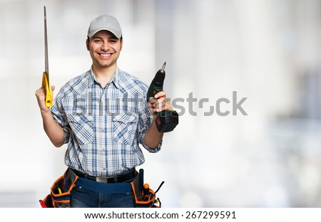 Portrait of a smiling carpenter holding wood planks. Bright background - stock photo