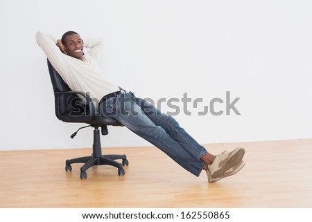 Portrait of a smiling casual Afro young man sitting on office chair in an empty room