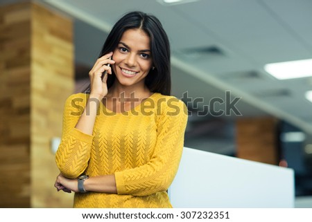 Portrait of a smiling casual businesswoman talking on the phone in office. Looking at camera - stock photo