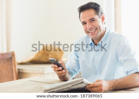 Portrait of a smiling casual man with newspaper and cellphone in the kitchen at home - stock photo