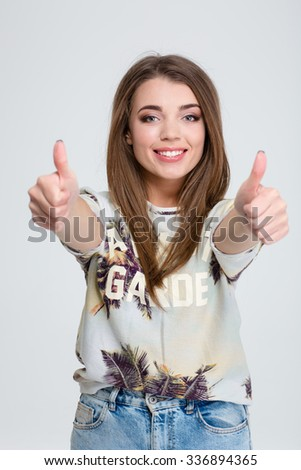 Portrait of a smiling casual woman showing thumbs up isolated on a white background - stock photo