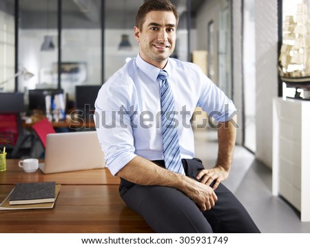 portrait of a smiling caucasian business executive sitting on desk in office. - stock photo