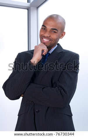 Portrait of a smiling charismatic businessman beside a window. - stock photo