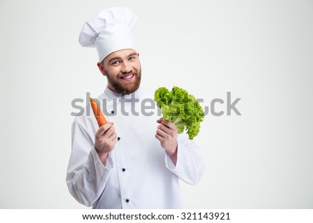 Portrait of a smiling chef cook holding salad and carrot isolated on a white background - stock photo