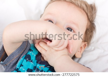 Portrait of a smiling child. A child on a white bed. Handsome boy.