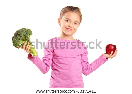 Portrait of a smiling child holding broccoli and apple isolated on white background