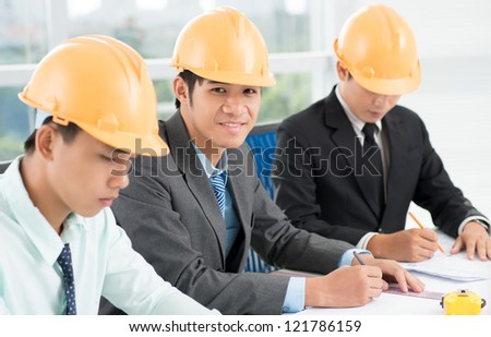 Portrait of a smiling civil engineer drawing a blueprint - stock photo