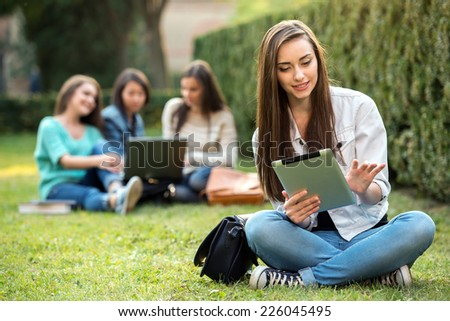 Portrait of a smiling college girl is holding tablet PC with blurred students are sitting in the park. - stock photo