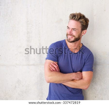 Portrait of a smiling confident guy with beard posing with arms crossed - stock photo