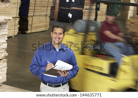 Portrait of a smiling confident man with clipboard in front of forklift in warehouse - stock photo