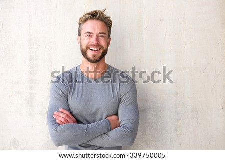 Portrait of a smiling cool guy with arms crossed - stock photo