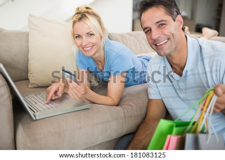 Portrait of a smiling couple doing online shopping through computer and credit card at home - stock photo