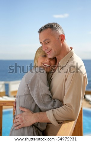 Portrait of a smiling couple embraced on a terrace