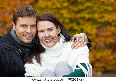Portrait of a smiling couple embracing in fall - stock photo