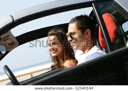 Portrait of a smiling couple in a car - stock photo