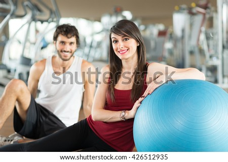 Portrait of a smiling couple in a gym - stock photo