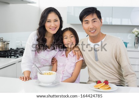 Portrait of a smiling couple with a daughter having breakfast in the kitchen at home