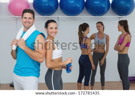 Portrait of a smiling couple with fitness class in background at gym - stock photo