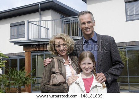 Portrait of a smiling couple with happy daughter standing outside new home