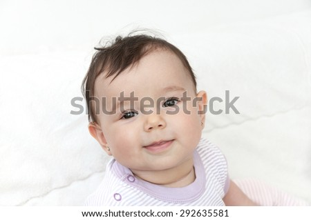 Portrait of a smiling cute baby girl. High key - stock photo