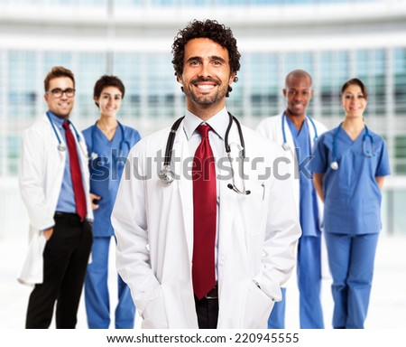 Portrait of a smiling doctor in front of his team - stock photo