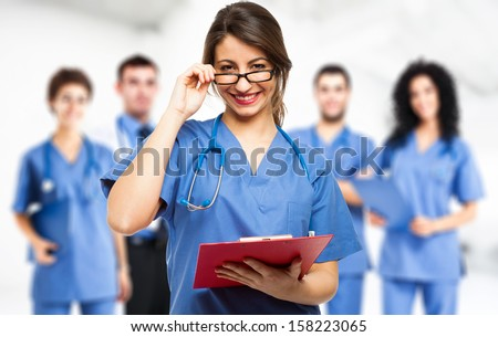 Portrait of a smiling doctor smiling doctor in front of her team - stock photo