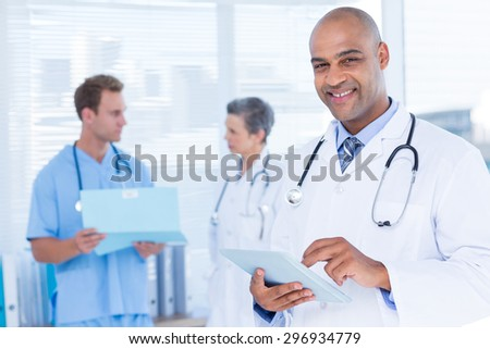 Portrait of a smiling doctor using his tablet - stock photo