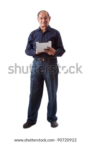 Portrait of a smiling elderly East Indian businessman using a digital tablet