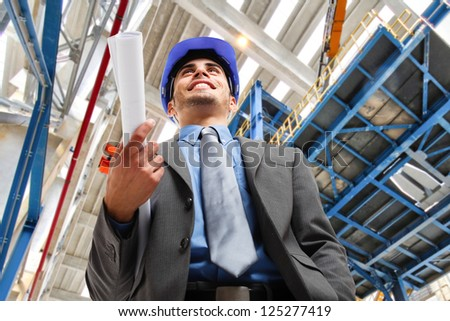 Portrait of a smiling engineer holding a blueprint - stock photo