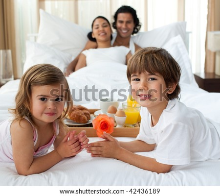 Portrait of a Smiling family having breakfast in the bedroom - stock photo