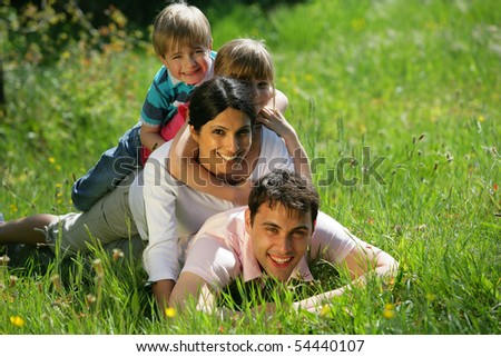 Portrait of a smiling family lying on the grass - stock photo
