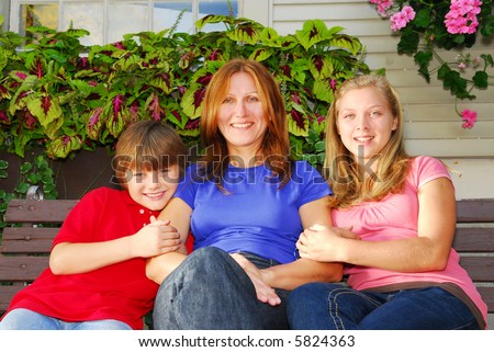Portrait of a smiling family - mother and children - in front of the house - stock photo
