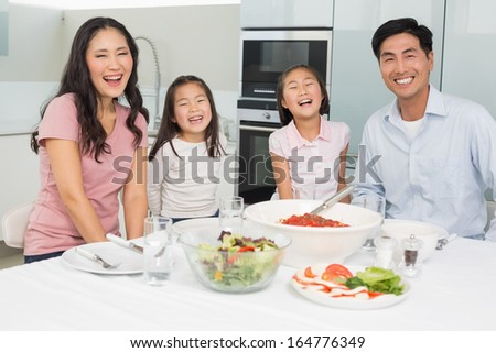 Portrait of a smiling family sitting at dining table in the kitchen at home