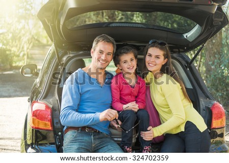 Portrait of a smiling family sitting in the trunk of their car on a country road. They are leaving for the weekend. They are wearing sunglasses and colored pulls. The girl is about ten years old