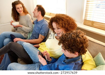 Portrait of a smiling family sitting on sofa enjoying time together - stock photo