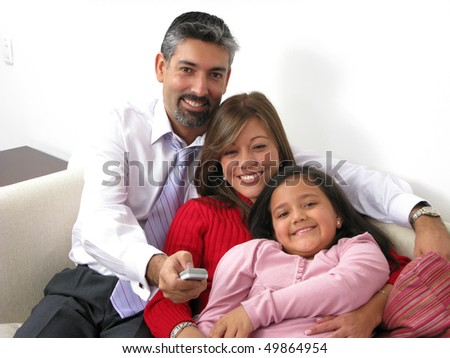 Portrait of a smiling family watching TV in the living room - stock photo