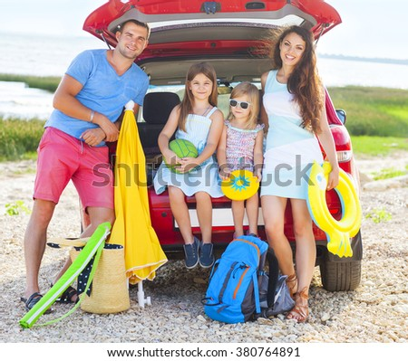 Portrait of a smiling family with two children at beach by car - stock photo
