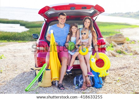 Portrait of a smiling family with two children at beach by car. Holiday and travel concept